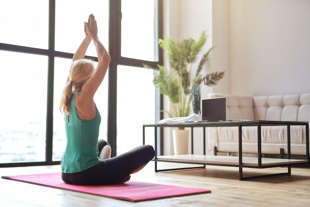 Sportowa dojrzała blondynka ćwicząca jogę, siedząca w pozycji lotosu na podłodze i obserwująca