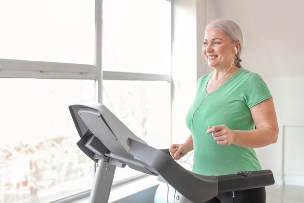 Sportowa dojrzała kobieta na bieżni w siłowni