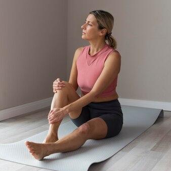 Sportowa dojrzała kobieta z różowym podkoszulkiem robi ćwiczenia treningowe