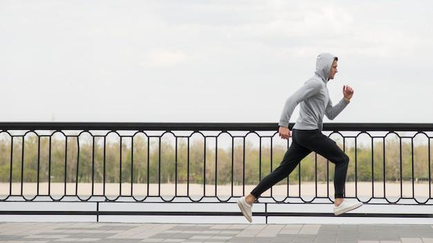 Sportowa dorosła samiec biega outdoors