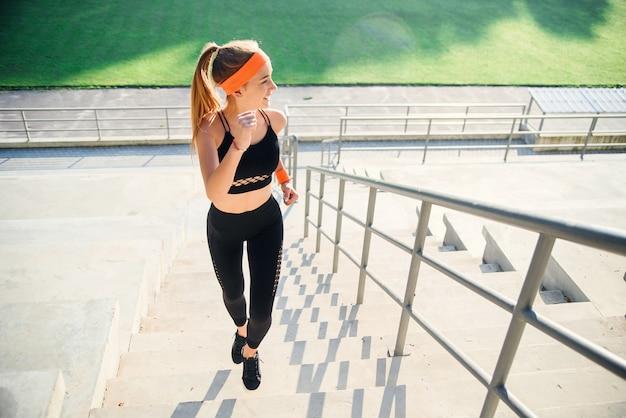 Sportowa dziewczyna działa szybko na schodach stadionu o wschodzie słońca. młoda kobieta w treningu sportowego na stadionie. bezpłatne miejsce na kopię.