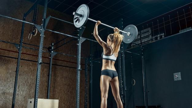 Sportowa dziewczyna fitness w ruchu robi trening w siłowni muskularny sport ciało z tyłu młodej wysportowanej kobiety