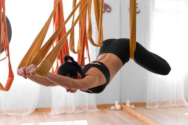 Sportowa dziewczyna lekkoatletycznego ćwiczy jogę latać na hamaku, rozciągając plecy i ramiona z bliska portret