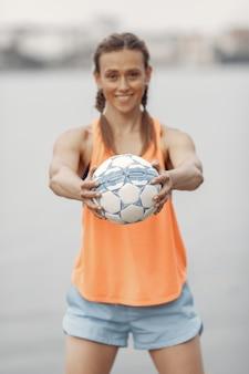Sportowa dziewczyna nad wodą. kobieta w letnim parku. pani w pomarańczowym stroju sportowym.