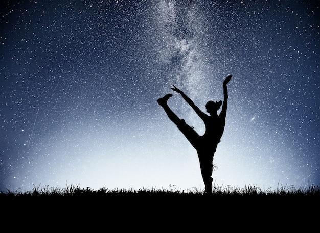 Sportowa dziewczyna o świcie uprawia jogę. zajęcia fitness na gwiaździstym niebie