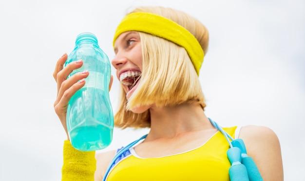 Sportowa dziewczyna pije wodę z butelki na tle nieba. picie podczas uprawiania sportu