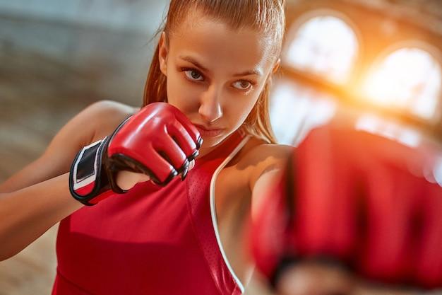 Sportowa dziewczyna robi ćwiczenia bokserskie, robiąc proste kopnięcie.