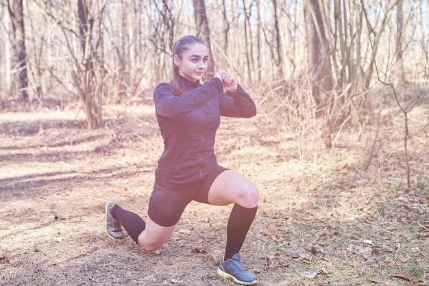 Sportowa dziewczyna robi przysiady w lesie