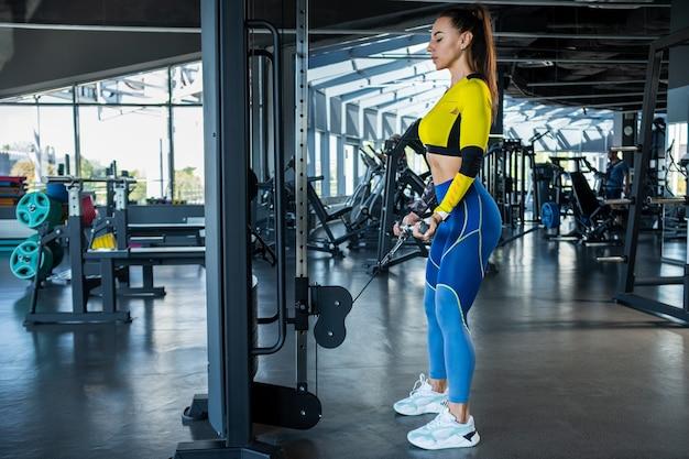 Sportowa dziewczyna robi zwijanie bicepsów na skrzyżowaniu kabli na siłowni