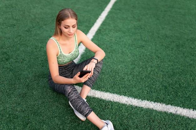 Sportowa Dziewczyna Siedzi I Używa Telefonu Premium Zdjęcia