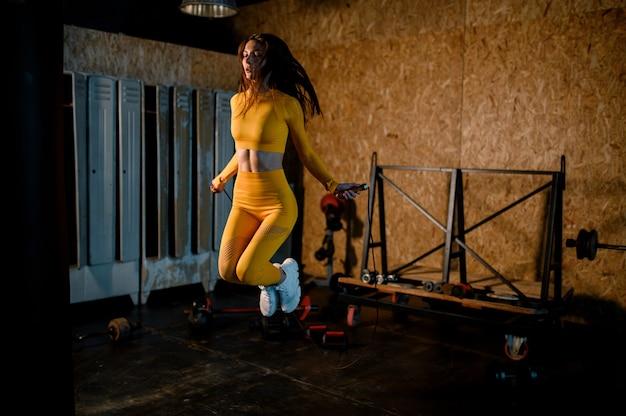 Sportowa dziewczyna skacze na linie na zdjęciach nowoczesnej siłowni w ruchu