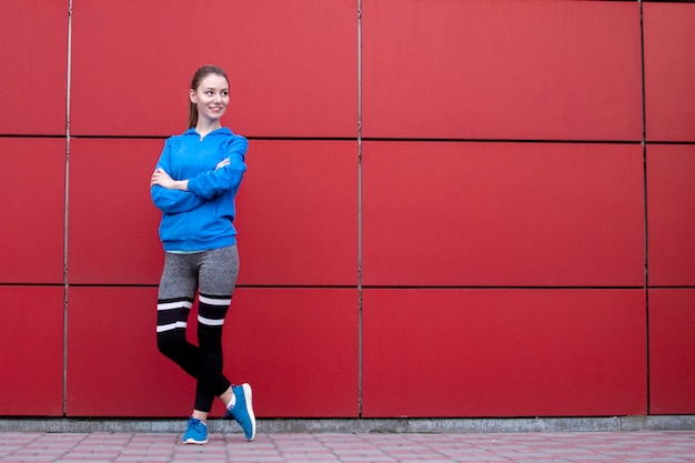 Sportowa dziewczyna stoi na czerwonej ścianie w odzieży sportowej