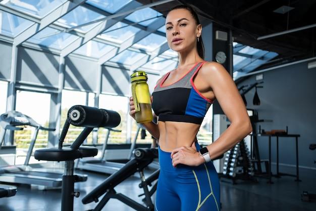 Sportowa dziewczyna stojąca w siłowni z butelką wody