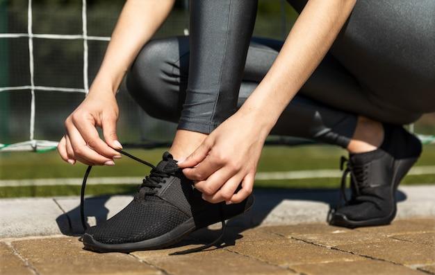 Sportowa dziewczyna sznurowanie jej trampki na zewnątrz