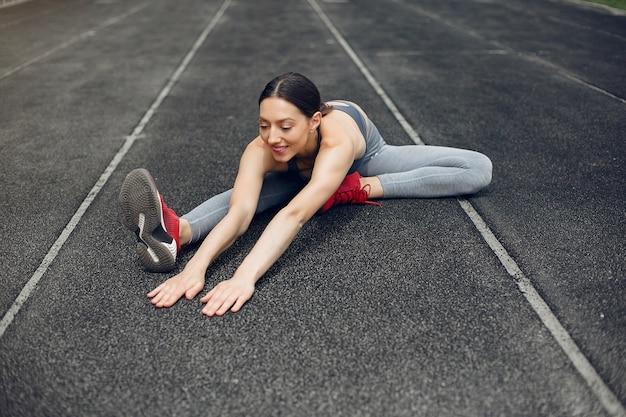Sportowa dziewczyna trenuje na stadionie