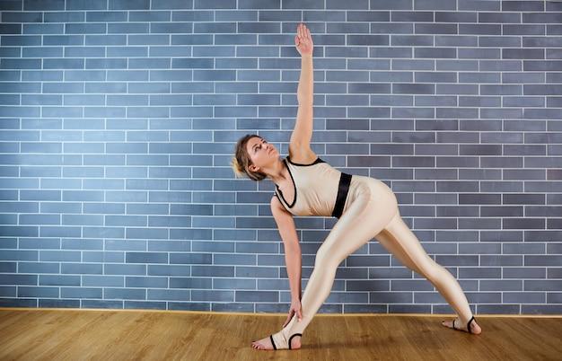 Sportowa dziewczyna w białym garniturze ćwiczy jogę na siłowni