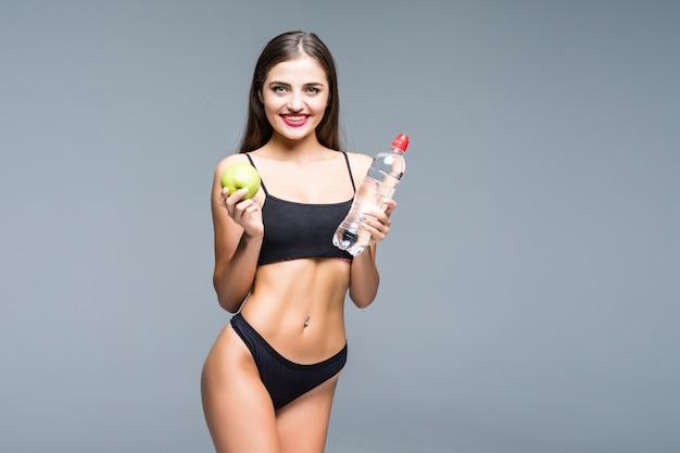 Sportowa dziewczyna w bieliźnie trzymając butelkę wody z zielonym jabłkiem i pokazując mięśnie na białym tle
