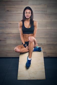 Sportowa dziewczyna w czarnym krótkim topie, szortach i rękawiczkach siedzi na drewnianym pudełku na siłowni