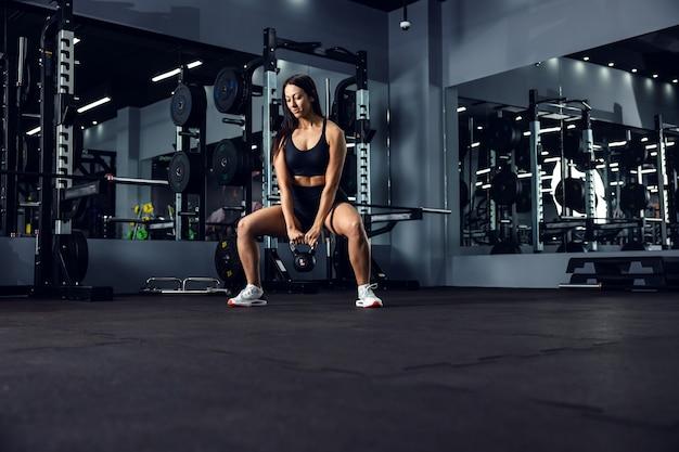 Sportowa dziewczyna w czarnym stroju sportowym ćwiczy cross-fit spalający kalorie na wewnętrznej siłowni, w której panuje mroczna atmosfera. jest w kucanej pozycji i trzyma w rękach dzwonek do czajnika. utrata masy ciała