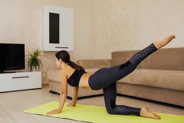 Sportowa dziewczyna w domu w odzieży sportowej trenuje na zielonym dywaniku do jogi.