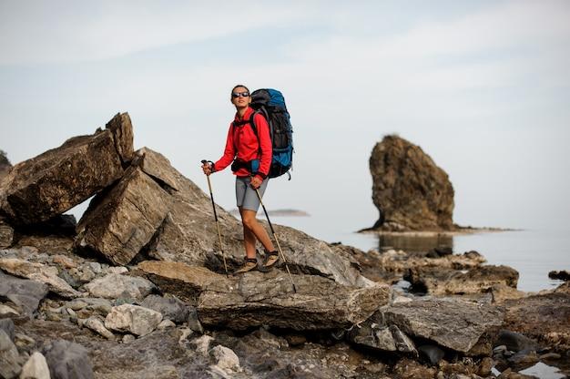 Sportowa dziewczyna w okularach stojących na skale wybrzeża nad morzem z plecakiem