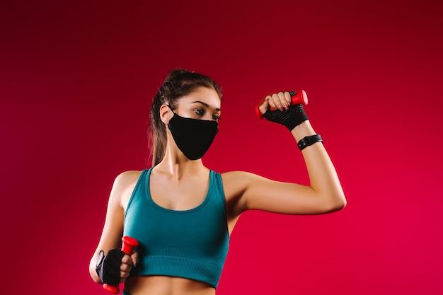 Sportowa dziewczyna w treningu medycznej maski ochronnej z hantlami na czerwonym tle wygląda na