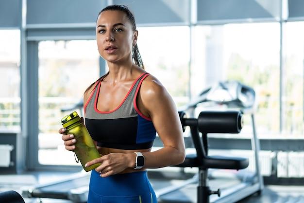 Sportowa dziewczyna wody pitnej po treningu na siłowni