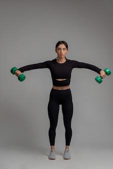 Sportowa dziewczyna wykonująca boczne podnoszenie hantli na szarej powierzchni