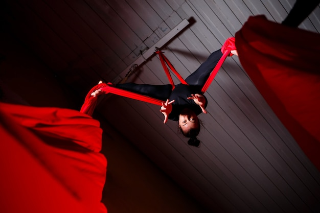 Sportowa dziewczyna wykonuje ćwiczenia gimnastyczne i cyrkowe na czerwonym jedwabiu. strzelanie studyjne na ciemnym tle. gimnastyka powietrzna na płótnie