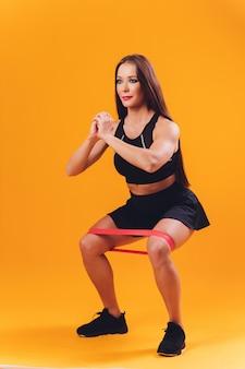Sportowa dziewczyna wykonuje ćwiczenia przy użyciu oporu. fotografia młoda dziewczyna na tle. siła i motywacja.
