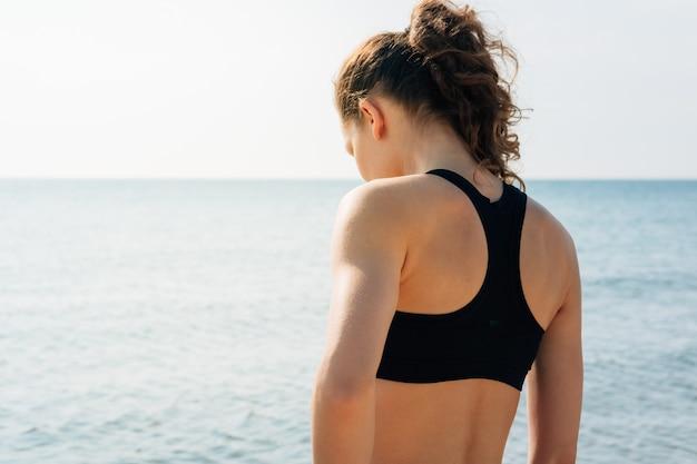 Sportowa dziewczyna z kędzierzawym włosy w sporta stanika pozyci na brzeg i patrzeć wodę przy wschodem słońca