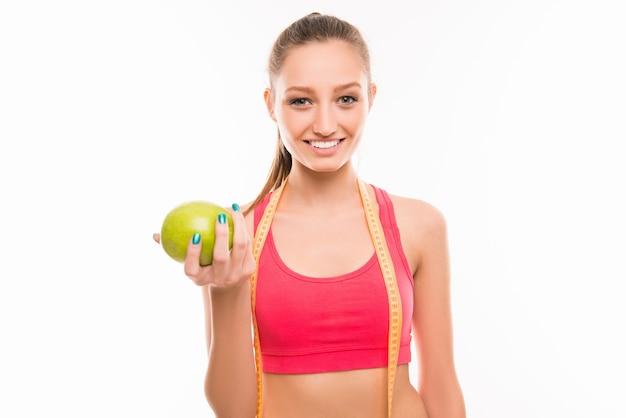 Sportowa dziewczyna z miarką i zielonym jabłkiem
