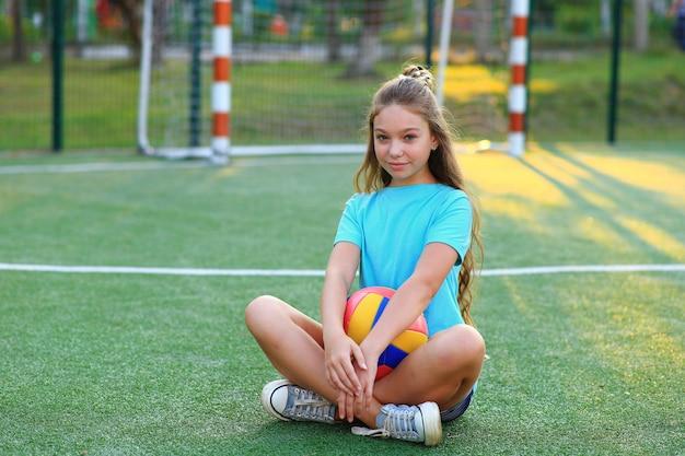 Sportowa dziewczyna z piłką na boisku