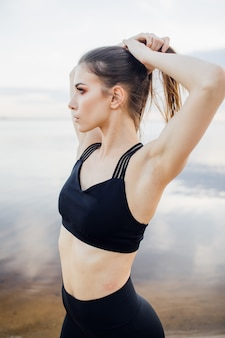 Sportowa dziewczyna z podkoszulkiem bez rękawów robi odcinek na plaży