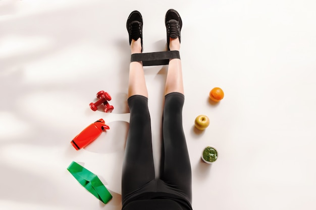 Sportowa dziewczyna z zdrowym jedzeniem na podłoga
