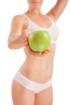Sportowa dziewczyna z zielonym jabłkiem w ręku.