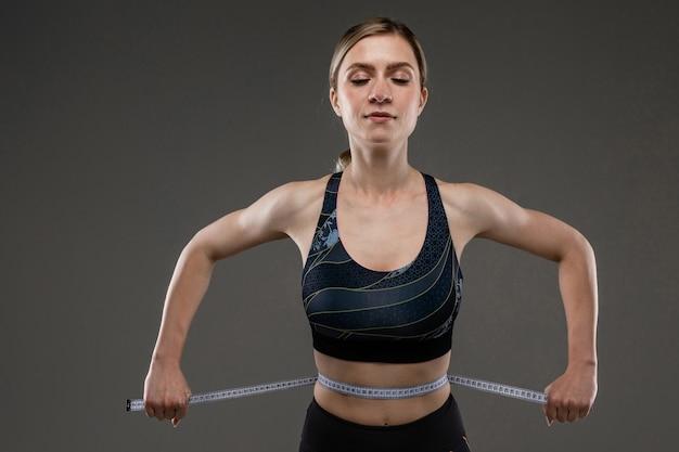 Sportowa dziewczynka kaukaski z szczupłą sylwetką mierzy talię na białym tle