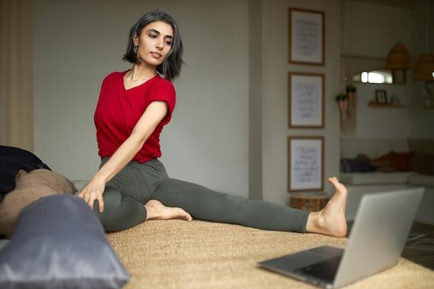 Sportowa, elastyczna młoda kobieta z kanalikami siedzi na podłodze, prostuje nogi, robi skręt kręgosłupa, patrzy na ekran komputera, ogląda samouczek wideo jogi online z instrukcjami krok po kroku
