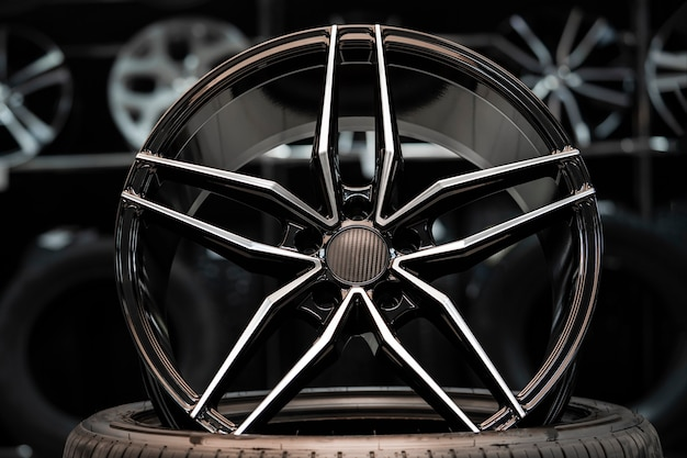 Sportowa felga aluminiowa z nakładką karbonową, w hali warsztatu samochodowego na tle felg. przedni widok.