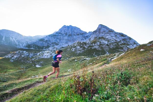 Sportowa górska kobieta jeździ po szlaku podczas treningu wytrzymałościowego