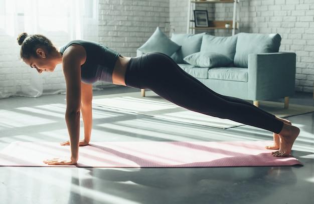 Sportowa kaukaski kobieta robi pompki w domu na macie do jogi w odzieży sportowej