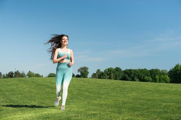 Sportowa kobieta biega plenerowego w parku