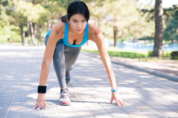 Sportowa kobieta biegacz w pozycji początkowej