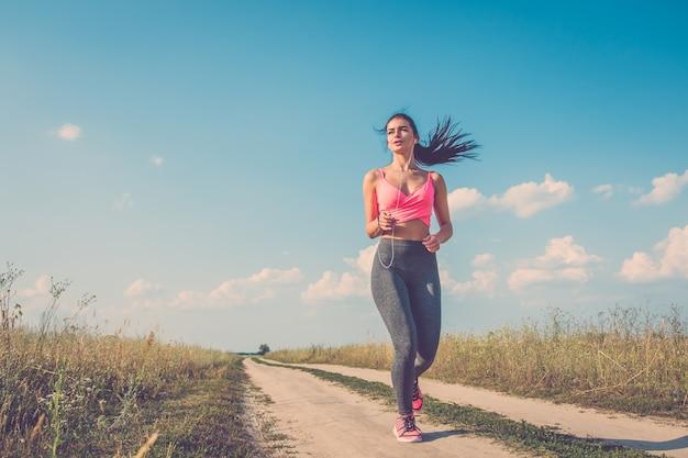 Sportowa kobieta biegająca po ścieżce w terenie