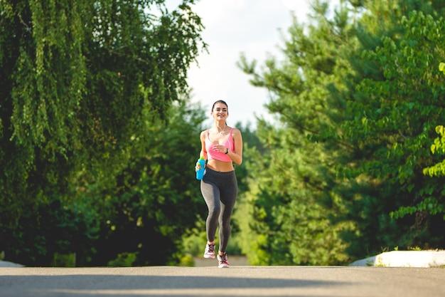 Sportowa kobieta biegająca z butelką na świeżym powietrzu
