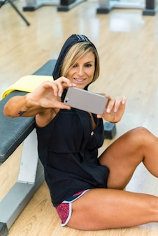 Sportowa kobieta co selfie na smartfonie w siłowni.