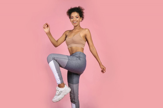 Sportowa kobieta ćwiczy ćwiczenia przysiadów w studio. afrykańska kobieta w sportowej pracy na różowym tle.