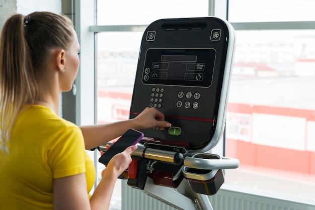 Sportowa kobieta dostosowuje ustawienia na bieżni w siłowni