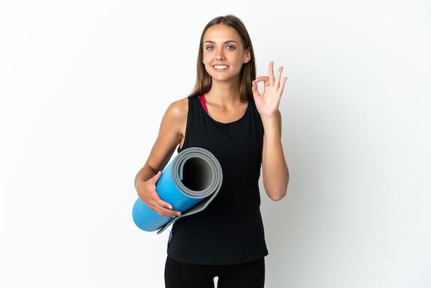 Sportowa kobieta idzie na zajęcia jogi, trzymając matę na białym tle pokazując znak ok palcami