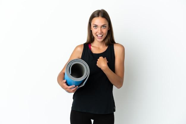 Sportowa kobieta idzie na zajęcia jogi, trzymając matę na białym tle z niespodzianką wyrazem twarzy
